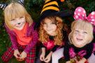 Three trick-or-treat girls looking at camera