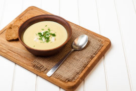 Broccoli cream soup on the white wooden table.
