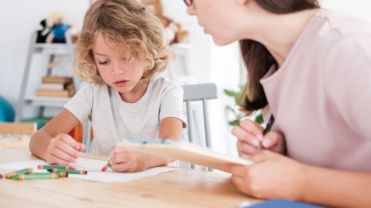 dziecko z blond kręconymi włosami i w białej koszulce siedzi przy stole z kobietą