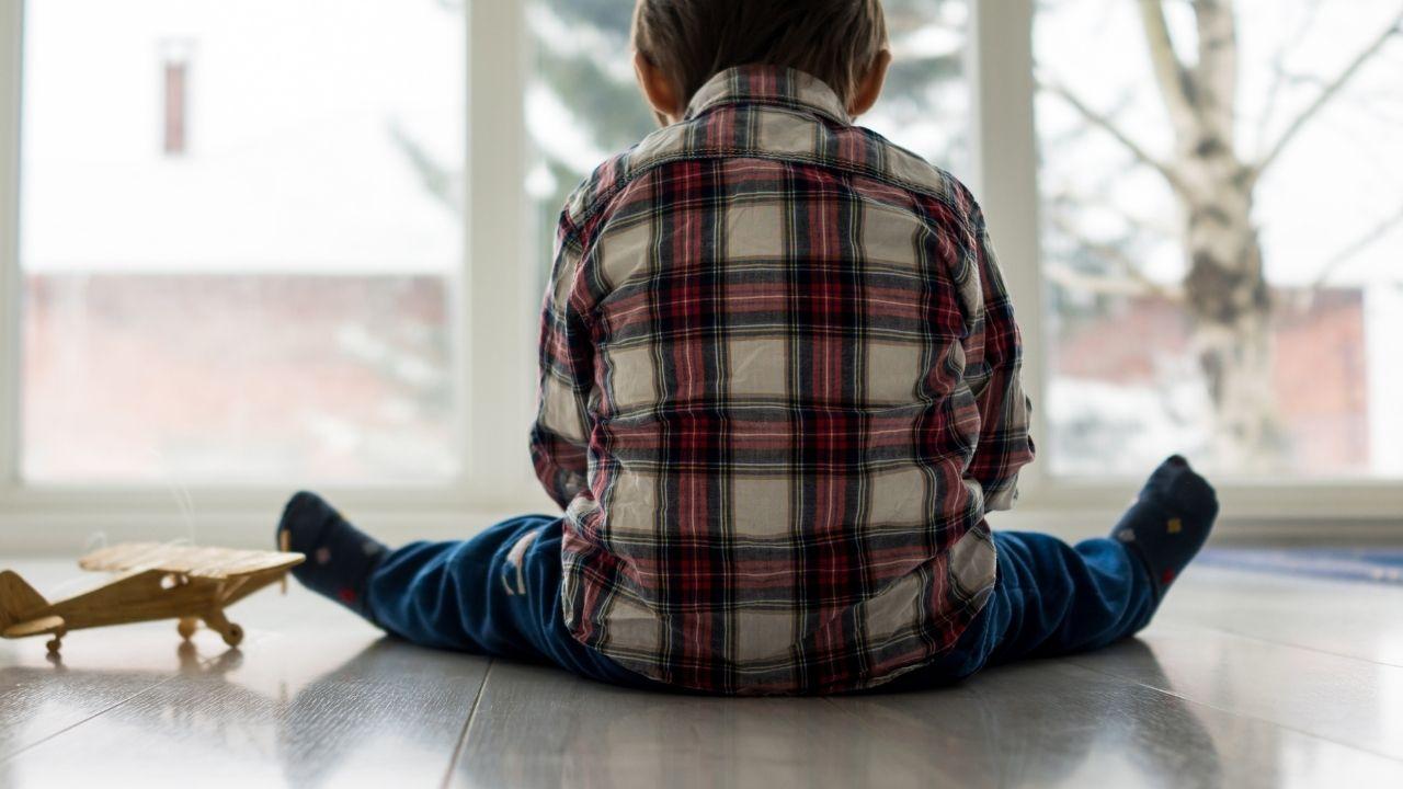 chłopiec w koszuli w kratę siedzący tyłem