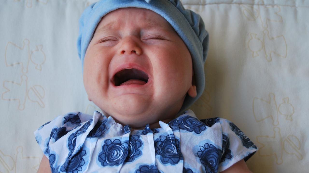 płaczące dziecko w niebieskiej czapce i niebieskim body