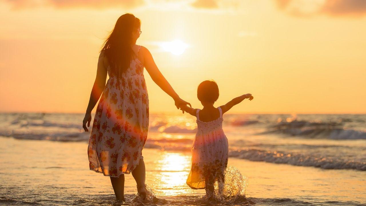 mama i córka spacerują plażą przy zachodzie słońca