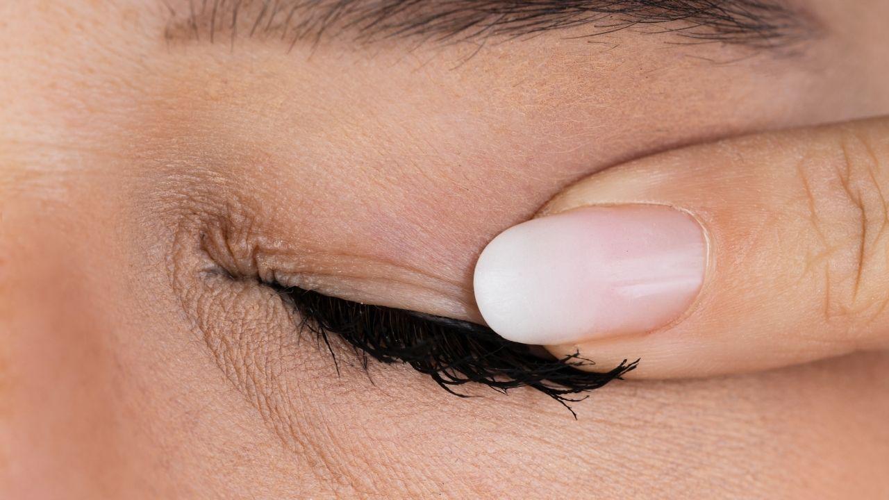 kobiecy palec przyciska linii rzęs na oku