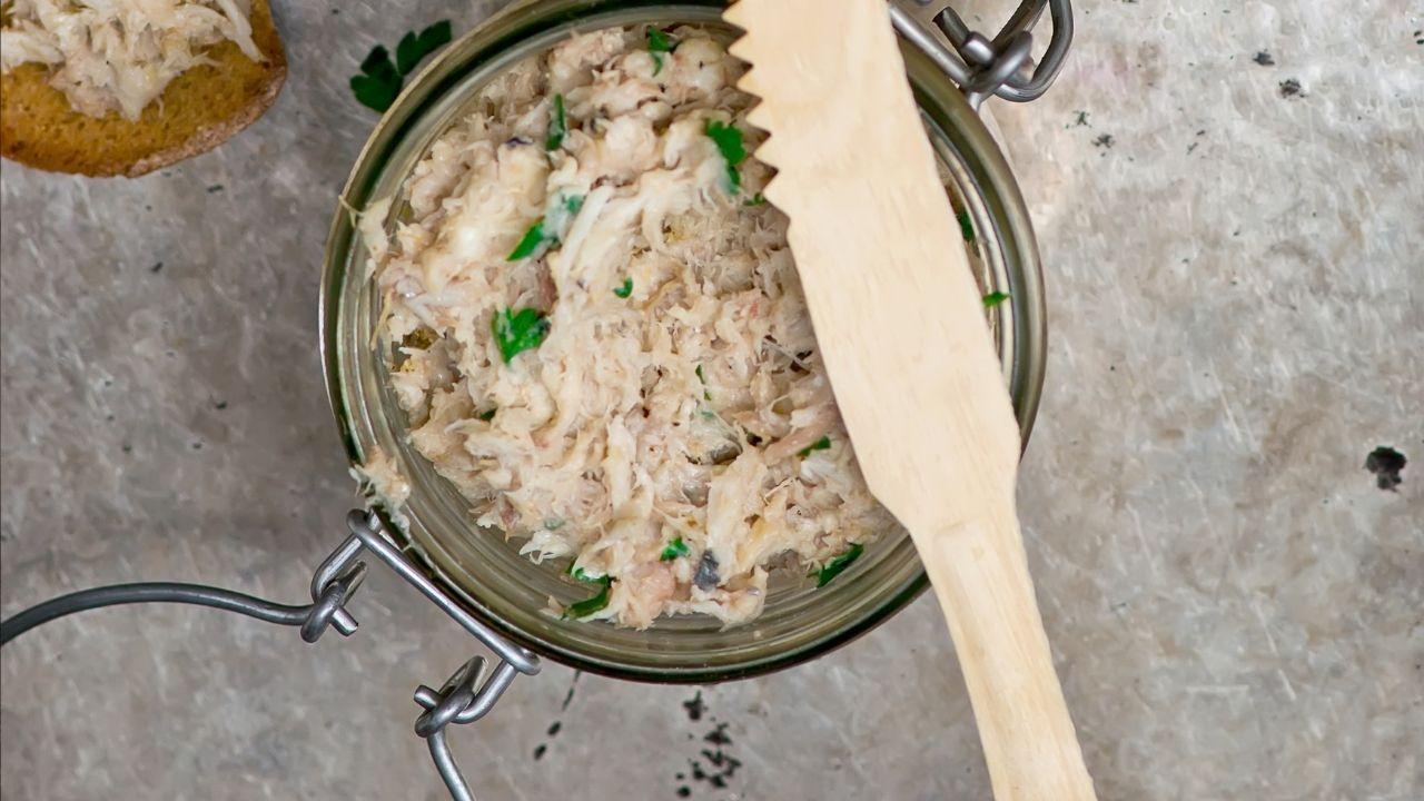 zbliżenie na pastę z makreli w szklanym słoiczku z drewnianym nożem