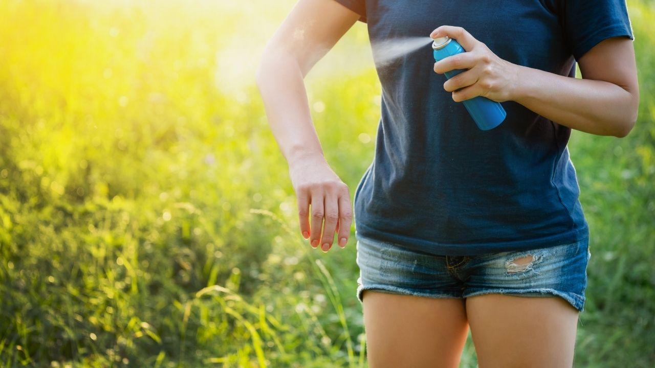 kobieta w krótkich spodenkach psika aerozol na rękę na tle polany