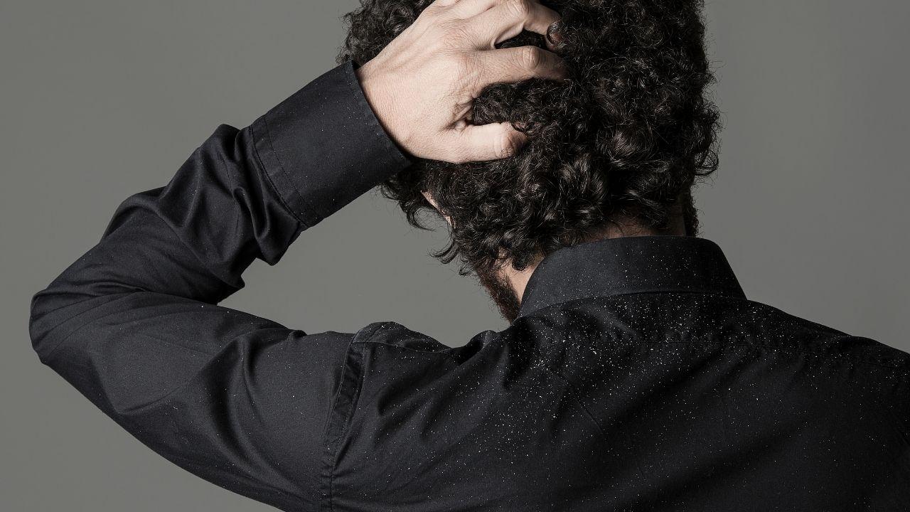 brunet stojący tyłem w czarnej koszuli łapie się za głowę