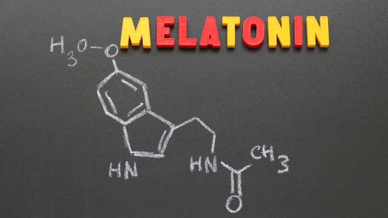 napis melatonina ułożony z czerwonych i żółtych literek na tablicy kredowej