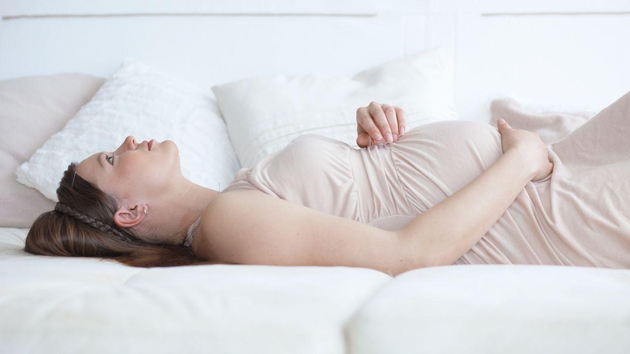 ciężarna kobieta leży na jasnej kanapie na plecach i trzyma się za brzuch