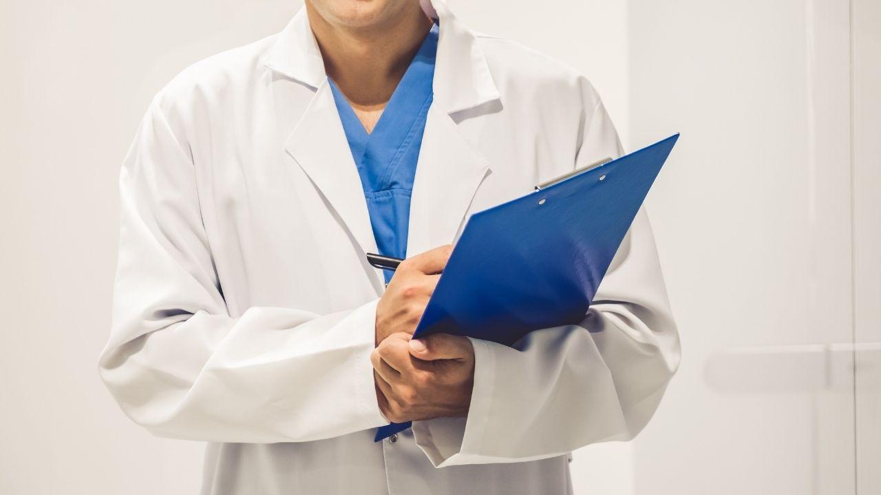 osoba ubrana w biały kitel trzyma niebieską teczkę