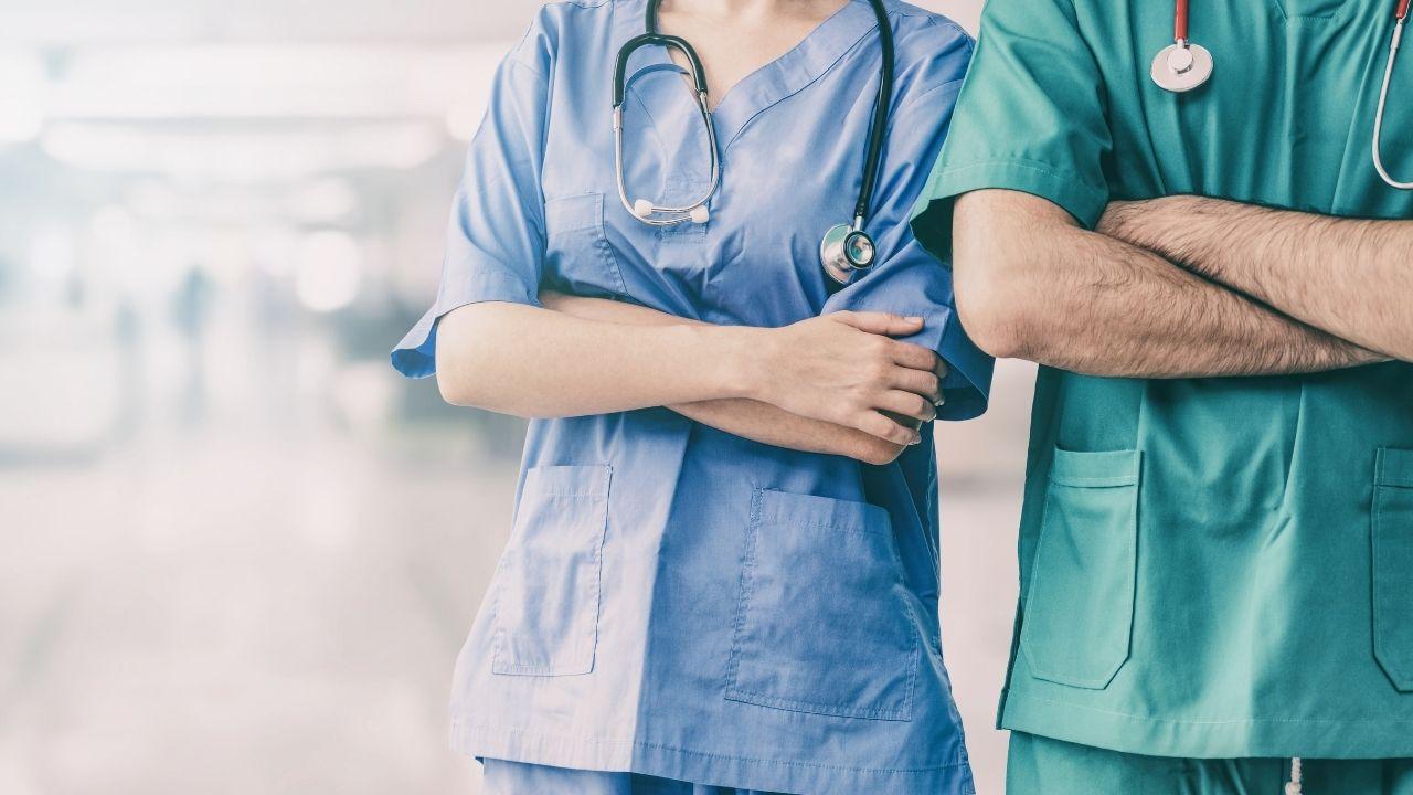 dwie osoby w strojach lekarzy stoją z założonymi rękoma na szpitalnym korytarzu