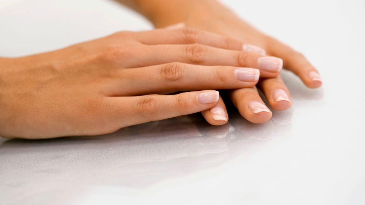 dłoń damska położona na drugiej dłoni