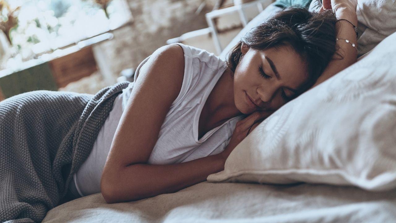 kobieta w białym t-shircie i szarych spodniach leży w pościeli w łóżku