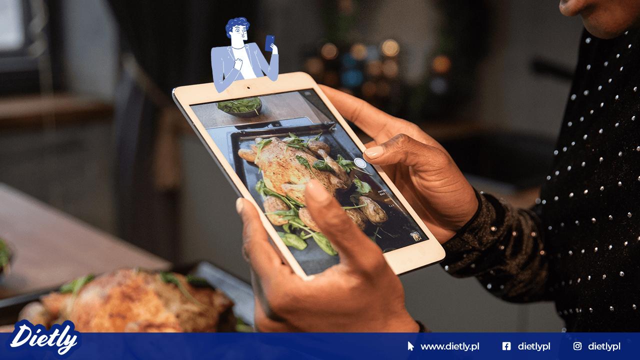 Osoba trzyma w dłoniach tablet ze zdjęciem przedstawiającym jedzenie