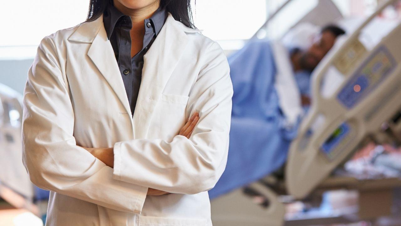 lekarka z założonymi rękoma i w kitlu stoi przed salą szpitalną a w tle widać szpitalne łóżko z chorym