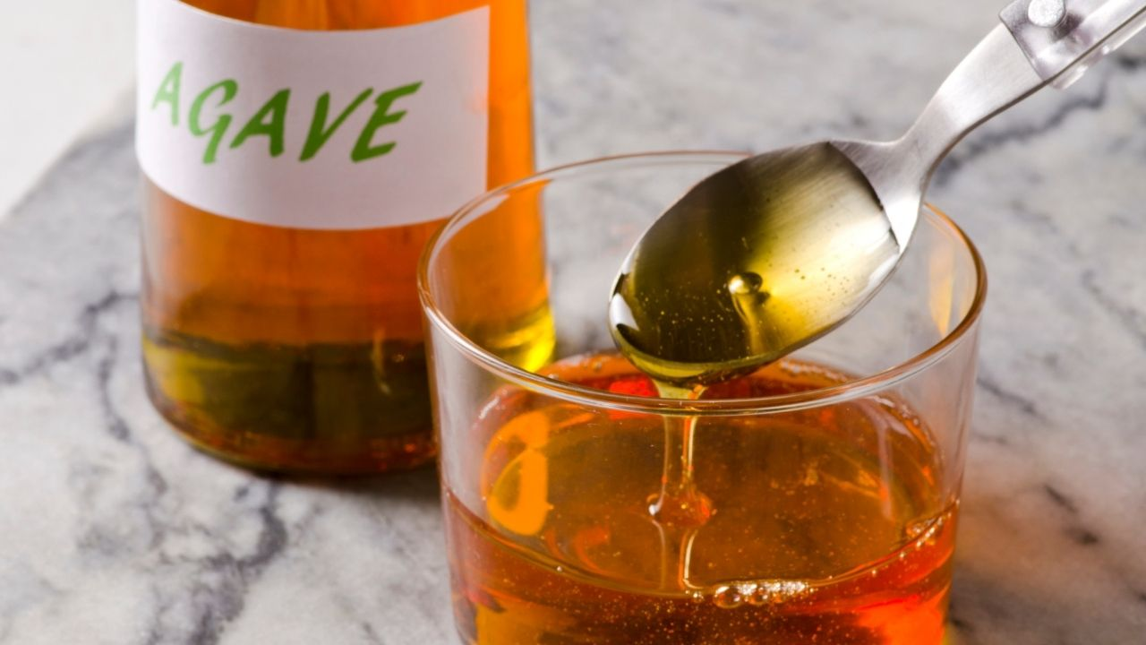 zbliżenie na syrop z agawy wylany na łyżeczkę. z której część wylewa się do szklanki