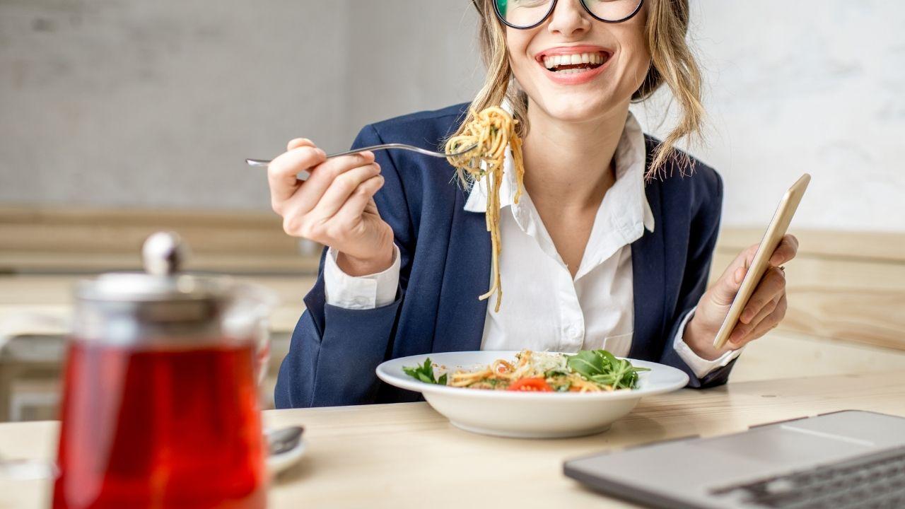 kobieta w okularach w marynarce je przy biurku obiad