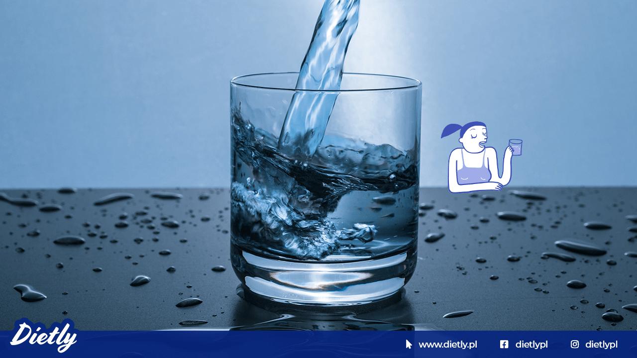 Na niebieskim tle szklanka napełniana wodą