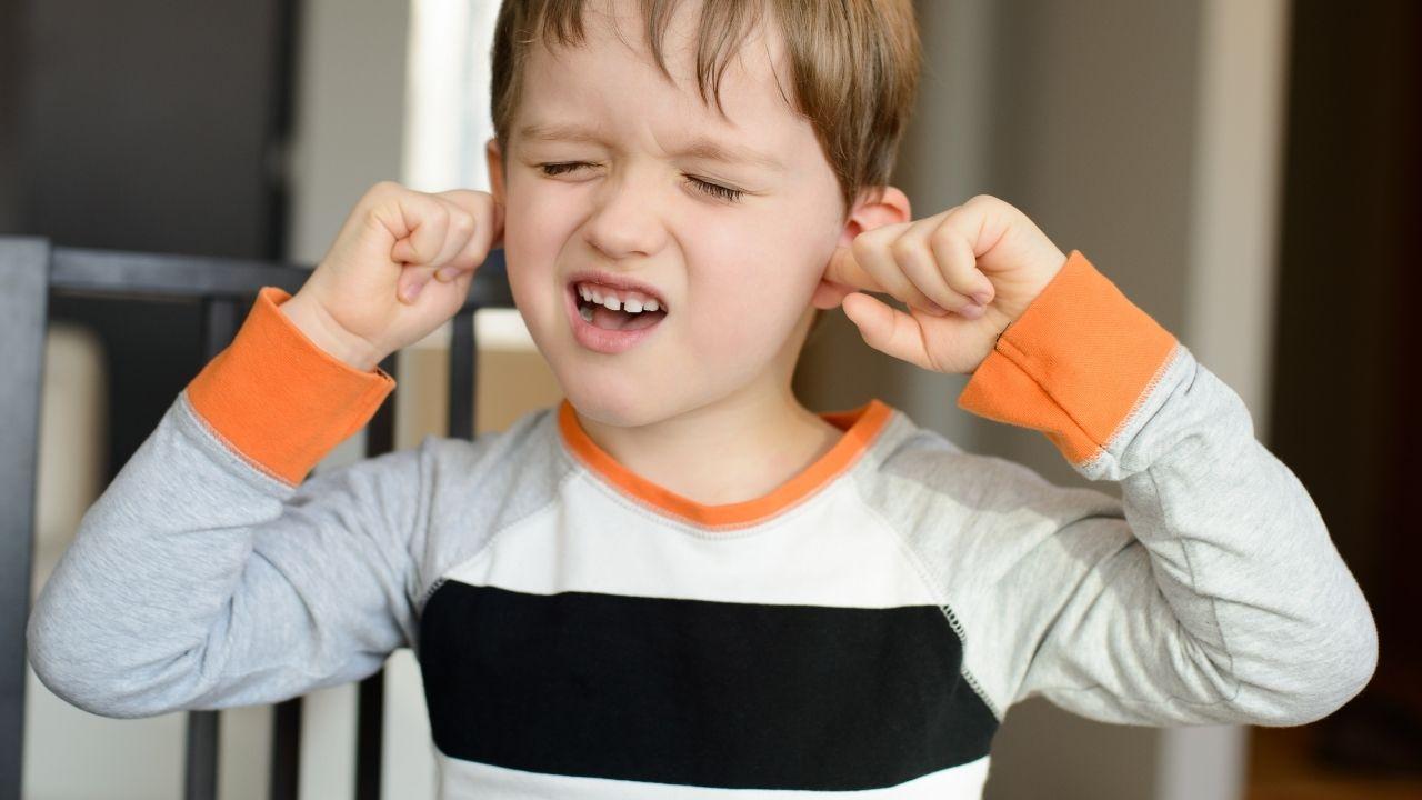 chłopiec z grymasem na twarzy wkłada palce do uszu